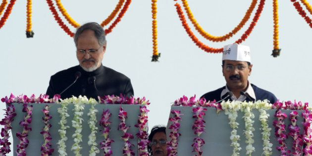 Anti-corruption champion and Aam Admi (Common Man) Party Leader Arvind Kejriwal (R) takes his oath of...