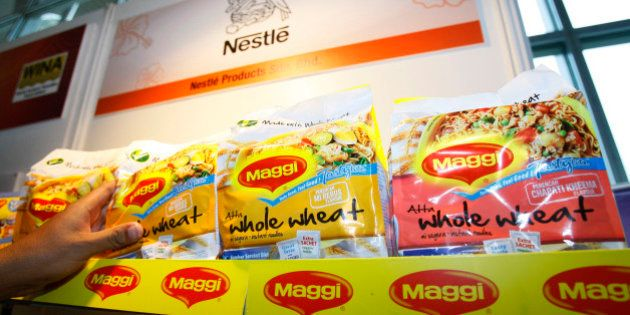 In this photo taken on April 21, 2010, a man picks up a package of Maggi instant noodle made of whole...