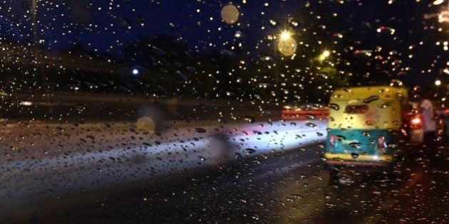 An Indian auto rickshaw is seen through a windshield of a car as a passenger gets on board while rain...