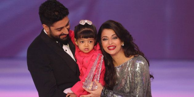 Former Miss World Aishwarya Rai, centre speaks on stage with husband Abhishek Bachchan and daughter Aaradhya...