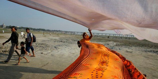 An Indian Hindu woman dries saris after taking ritualistic holy dip in the river Ganges, in Allahabad,...