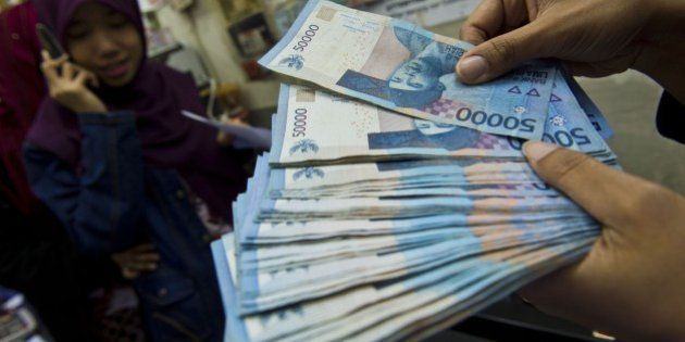 A money changer prepares Indonesian rupiah bills for a customer in Jakarta on March 13, 2015. According...