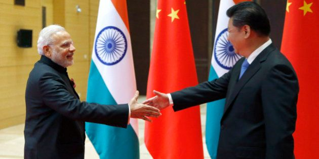 Indian Prime Minister Narendra Modi, left, is welcomed by Chinese President Xi Jinping prior to their...