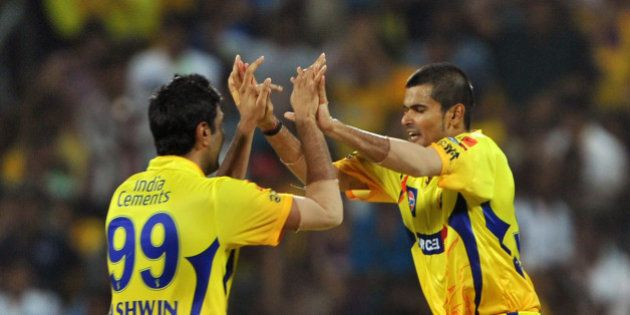 Chennai Super Kings fielder Badrinath (R) celebrates with his teammate after taking a catch to dismiss...