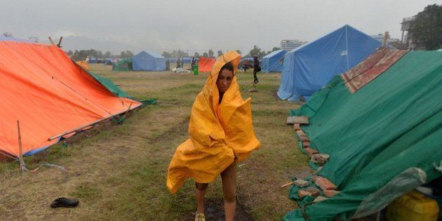 A Nepalese residents walks during a downpour at a relief camp for earthquake survivors in Kathmandu on...