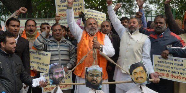 Rashtrawadi Shiv Sena (RSS) leader, Jai Bhagwan Goyal(C), with party activists, holds the effigies...