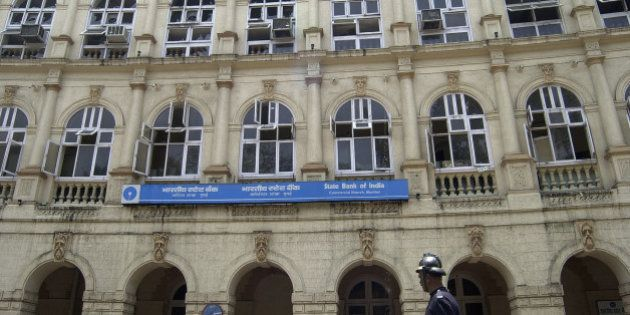 A fire fighter passes by a heritage building, which houses State bank of India, after it was partially...