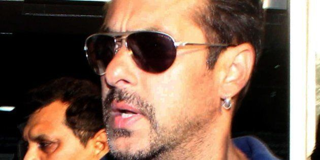 Indian Bollywood actor Salman Khan walks with officials as he arrives at an airport in Mumbai on May...