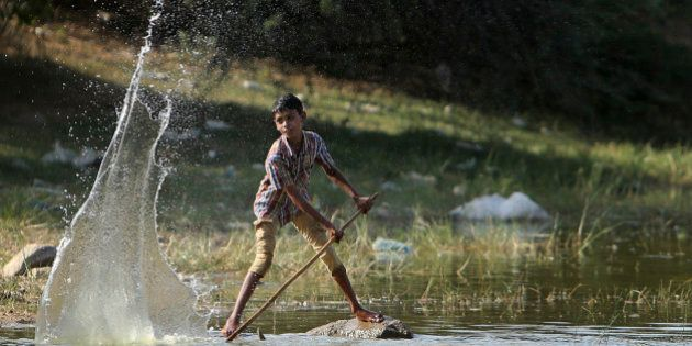 An Indian boy plays with water at a pond on a hot summer day in Hyderabad, India, Sunday, May 24, 2015....