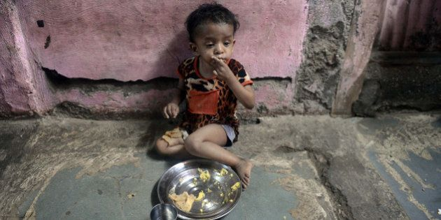 A malnourished Indian child finishes her lunch consisting of a special supplementary diet at the Nutrition...