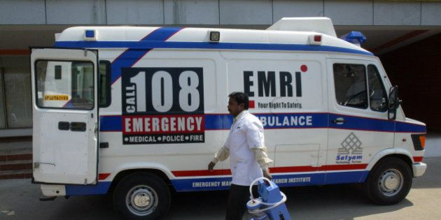 An Indian medical technician walks past an Emergency Management and Research Institute (EMRI) ambulance...
