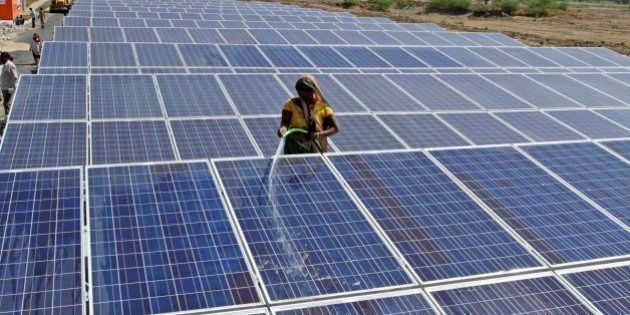 An Indian worker cleans installed solar panels atop the Narmada canal ahead of its inauguration at Chandrasan...
