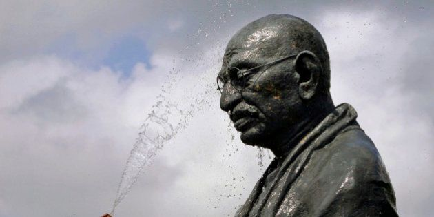 A worker sprays water on a statue of the late Mahatma Gandhi on the eve of his birth anniversary at Gandhi...