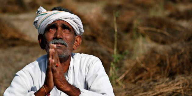 An Indian farmer looks skyward as he sits in his field with wheat crop that was damaged in unseasonal...