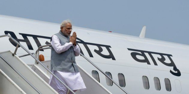 Indian Prime Minister, Narendra Modi gives a traditional greeting as he exits the plane on his arrival...