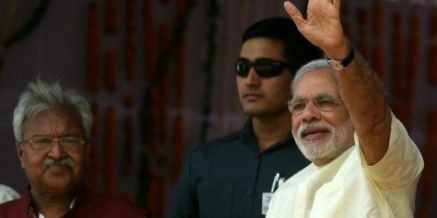 Indian Prime Minister Narendra Modi gestures to the crowd as he arrives at a rally venue in Mathura on...