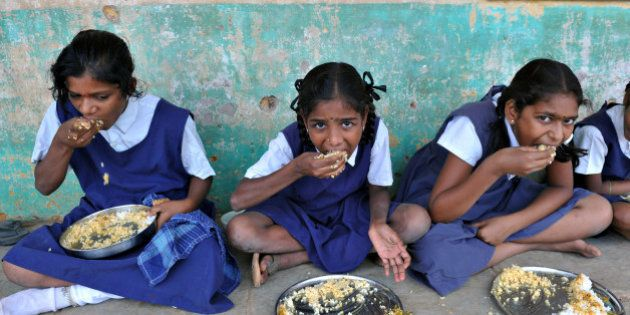 Indian schoolchildren eat their mid-day meal at a government primary school in the outskirts of Hyderabad on June 13, 2011, on the opening day of the new academic year. The government of India's Andhra Pradesh state has introduced English as a second language from Class 1 onwards for the 2011-2012 academic year. India's National Knowledge Commission has admitted that no more than one percent of country's population uses English as a second language. AFP PHOTO/Noah SEELAM (Photo credit should read NOAH SEELAM/AFP/Getty Images)