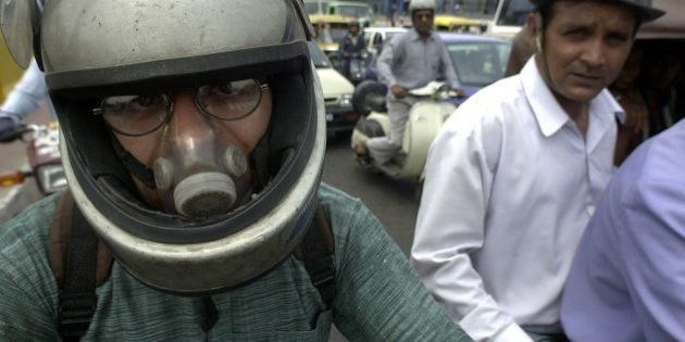 NEW DELHI, INDIA: A Delhi motorcyclist wears an air-filter while waiting for the light to change at a...