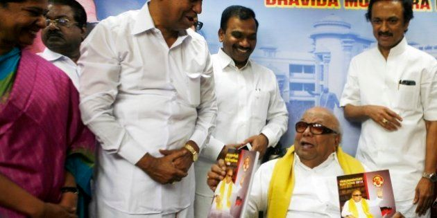 Leader of the Dravida Munnetra Kazhagam party M. Karunanidhi, seated, releases his party's election...