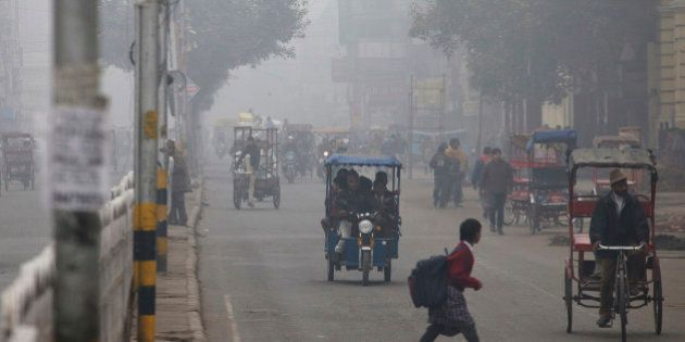 A schoolgirl crosses a road shrouded in haze in New Delhi, India, on Monday, Jan. 20, 2014. India, China...