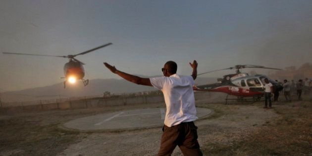 An airline ground staff member directs a chopper carrying the bodies of victims of a helicopter crash...