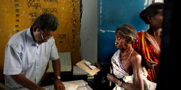 FILE - In this March 20, 2012 file photo, a tribal woman shows her ration card to receive coupons to...