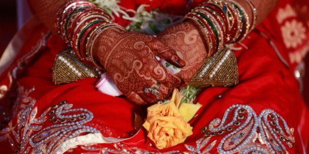 An Indian Muslim bride, her hands decorated with henna, attends a mass wedding organized by a social...