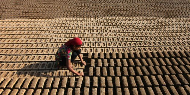 An Indian woman laborer works at an earthen brick factory on Earth Day on the outskirts of Jammu, India,...