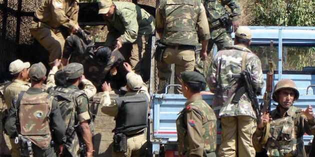 Imphal, INDIA: Indian army personnel lift the body of a policeman from a truck in the grounds of The...