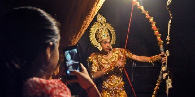 An Indian woman takes a photograph on her mobile of an artist dressed as Lord Rama as he waits backstage...