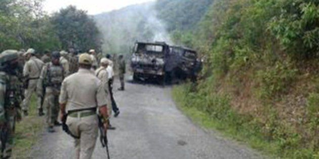 This photograph taken on June 4, 2015 shows Indian security personnel and smoldering vehicle wreckage...