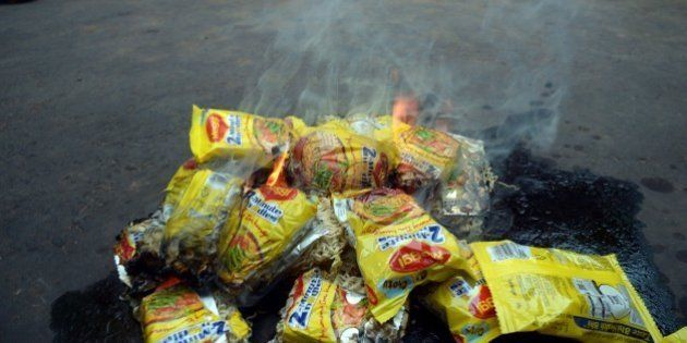Indian social activists burn packets of Nestle's Maggi instant noodles during a protest in Kolkata on...