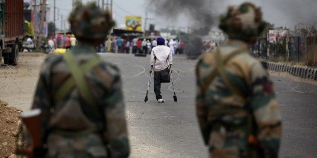 Indian policemen confront protestors across a barbed wire barricade during a curfew in Jammu on June...
