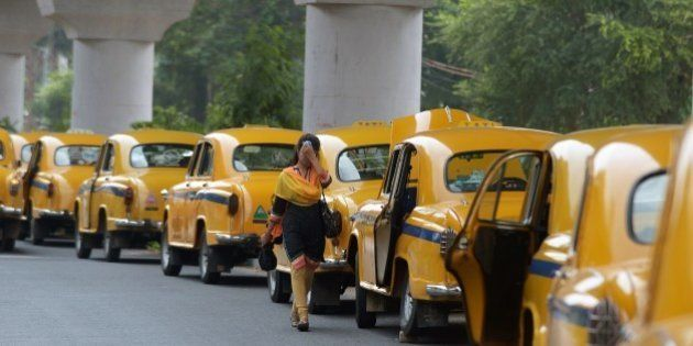 An Indian pedestrian walks past parked taxis in Kolkata on May 25, 2015. More than 430 people have died...