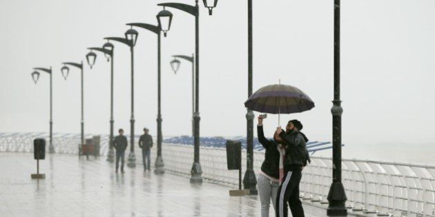 A Lebanese couple takes a selfie under the rain as they walk at Beirut's seaside corniche in Ain al-Mreisseh...