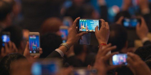 India's Prime Minister Narendra Modi is seen on mobile phone screens while he delivers a speech at the...