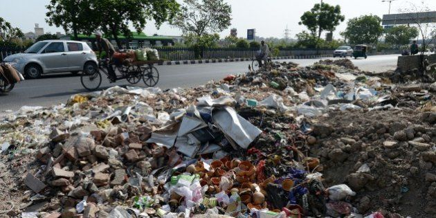 Heap of garbage are strewn along the roadside as sanitation workers strike in New Delhi on June 11, 2015....
