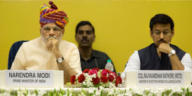 Indian Prime Minister Narendra Modi, left, sits with junior Minister for Information and Broadcasting...