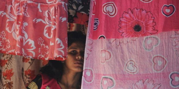 An Indian sex worker looks on past curtains in the red light district of Kamathipura in Mumbai on August...