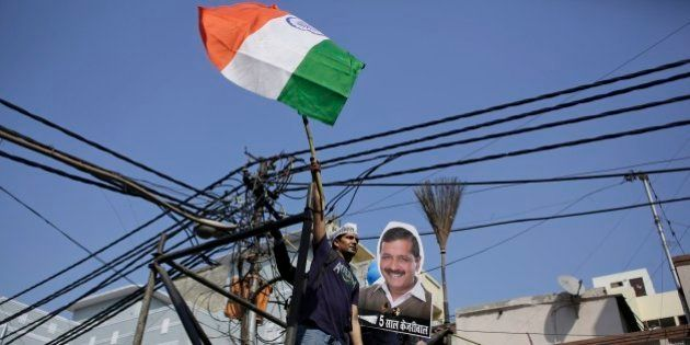 A supporter of the Aam Aadmi Party, or Common Man's Party, waves the Indian flag next to a portrait...