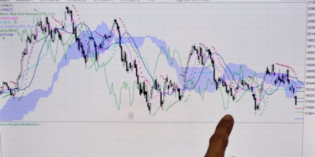 An Indian stockbroker refers to a graph showing the movement of the SENSEX in the year 2011 as he monitors...