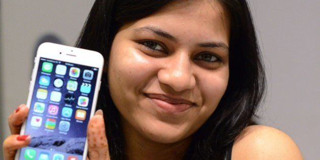 An Indian customer poses with her brand new Apple iPhone 6 at the Unicorn Infosolutions Apple Premium...