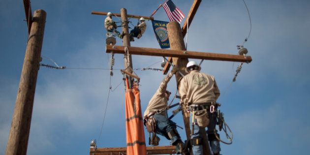 TULARE, CA - FEBRUARY 10: Linemen climb poles at the Southern California Edison exhibit on opening day...