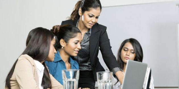 Indian women business colleagues working around a