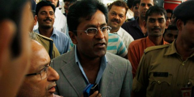 Suspended Indian Premier League Chairman Lalit Modi, center, is surrounded by bodyguards, media, and...