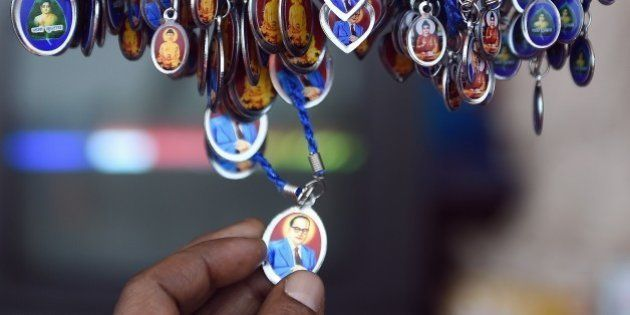 A man inspects a locket with an image of Bhimrao Ambedkar for sale on Ambedkar's 124th birth anniversary...