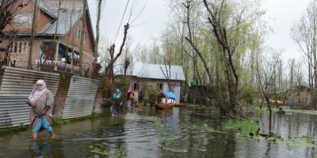 Kashmiri residents walk through floodwaters outside their homes as water levels rise on Dal Lake in Srinagar...