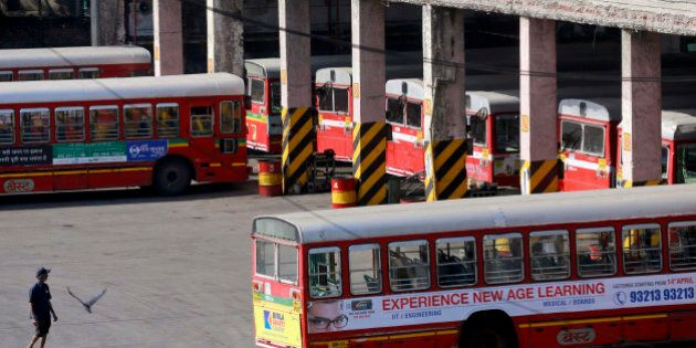 A man walks past parked buses at a station during a bus strike in Mumbai, India, Wednesday, April 2,...