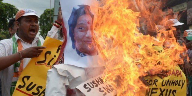 Congress supporters shout anti-Bharatiya Janata Party (BJP) slogans as they burn effigies of External...