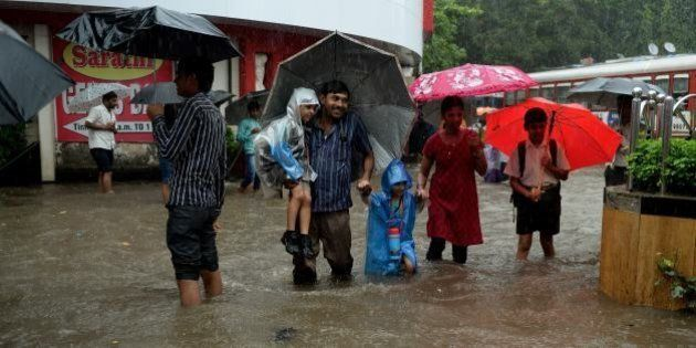 Indians walk through a flooded street during rain showers in Mumbai on July 23, 2013. The Mumbai city...